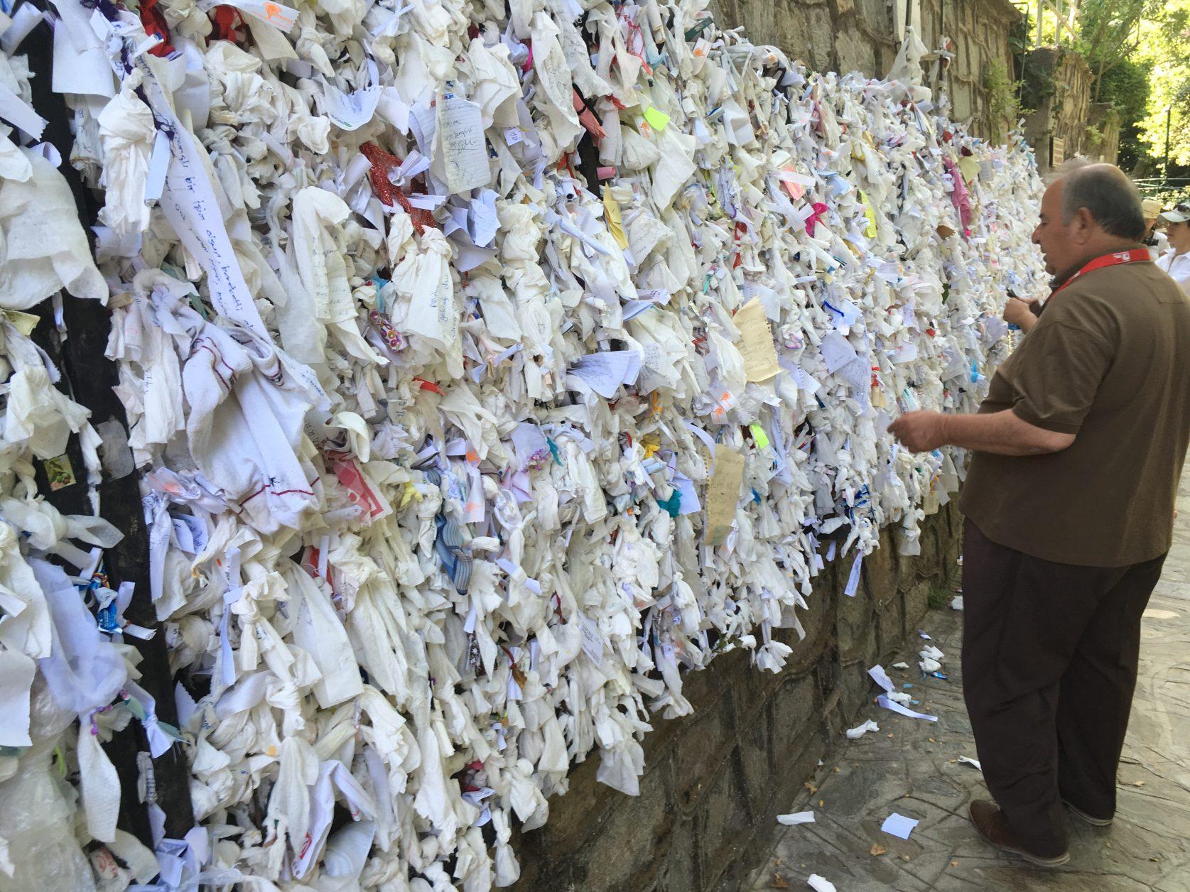 An der Mauer der Brunneneinfassung befestigen Pilger tausende von Zetteln mit ihren Gebetswünschen.